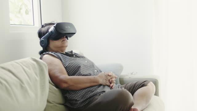 senior woman using vr headset virtual reality simulator - woman cross legged stock videos & royalty-free footage