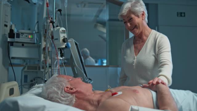 ds 年配の女性夫の訪問がある icu 手術後 - 気にかける点の映像素材/bロール