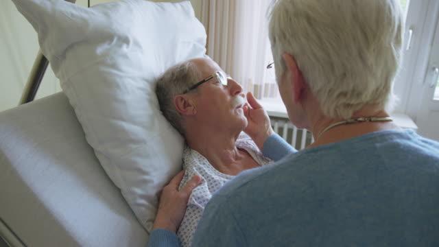 vídeos y material grabado en eventos de stock de mujer mayor visitando a un marido enfermo en la sala del hospital - visita