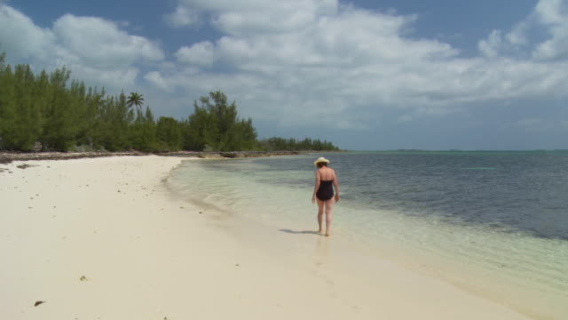 WS, Senior woman wading in ocean, rear view, Abaco Islands, Bahamas