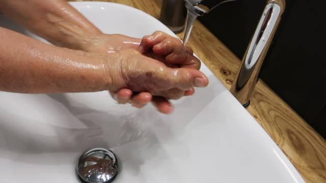 vídeos y material grabado en eventos de stock de mujer mayor wahing sus manos - frotar