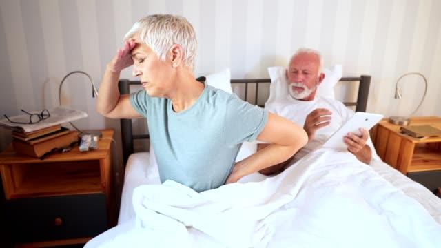 vídeos de stock, filmes e b-roll de mulher sênior acordando com dores ao lado de seu marido na cama - rim humano