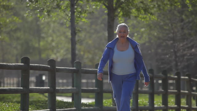 MS PAN Senior woman walking along path in park / Los Angeles, California, USA
