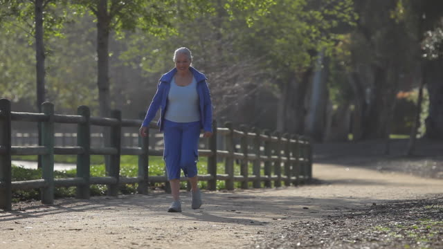 WS PAN Senior woman walking along path in park / Los Angeles, California, USA