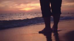Senior Woman Walking Along the Beach with Sunset/Sunrise Background