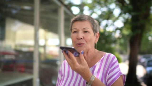 vídeos de stock, filmes e b-roll de idosa andando e falando no celular na cidade - mulheres idosas