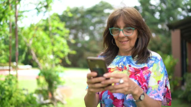 senior woman walking and using mobile phone at home - argentinian ethnicity stock videos & royalty-free footage