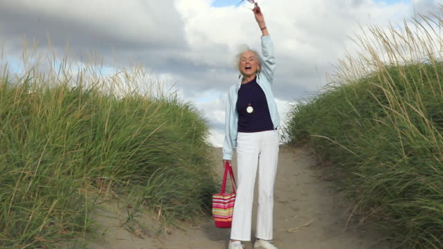 ws senior woman walking down dune slope towards beach / portland, oregon, usa - waving stock videos & royalty-free footage