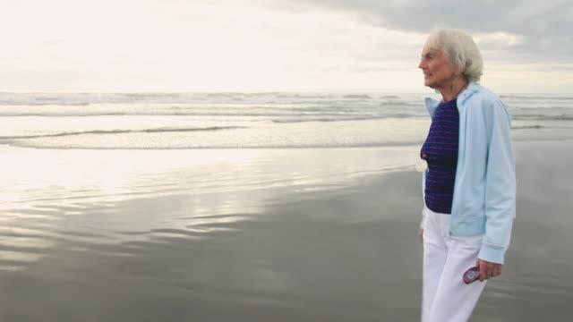 WS TS Senior woman walking on beach / Portland, Oregon, USA
