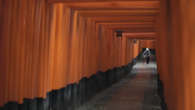 WS Senior woman walking under Torii gates leading to inner Fushimi Inari Taisha shrine, Kyoto, Japan