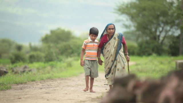 Senior woman walking with her grandson, Malshej Ghat, Maharashtra, India