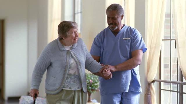 vidéos et rushes de ms senior woman walking with male nurse down hospital hallway as another man walks by / washington state, usa - infirmier