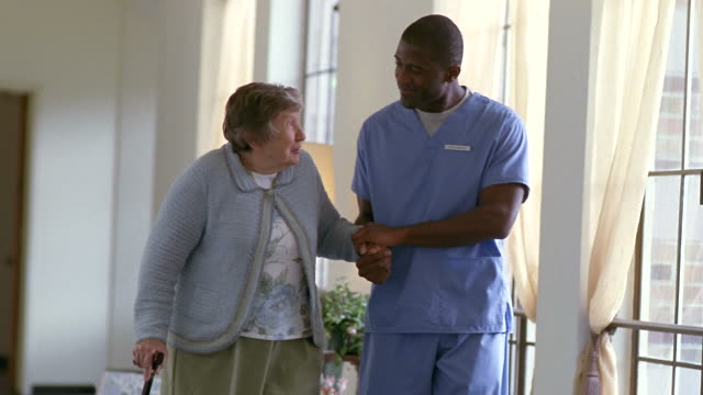 ms senior woman walking with male nurse down hospital hallway / washington state, usa - nurse stock videos & royalty-free footage