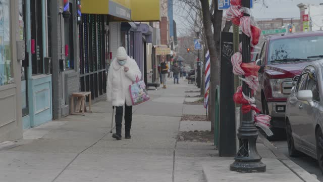 senior woman walks on eastern avenue wearing a mask during the coronavirus pandemic on december 26, 2020 in baltimore, maryland. according to the... - senior women stock videos & royalty-free footage