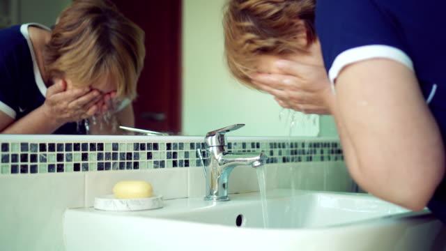 senior woman washing face - washing face stock videos & royalty-free footage