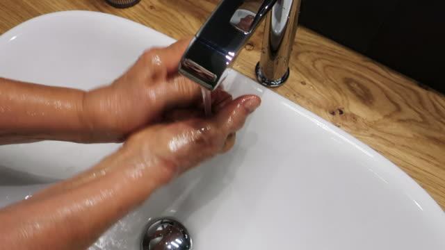 vídeos y material grabado en eventos de stock de mujer mayor lavando sus manos bajo agua del grifo - frotar