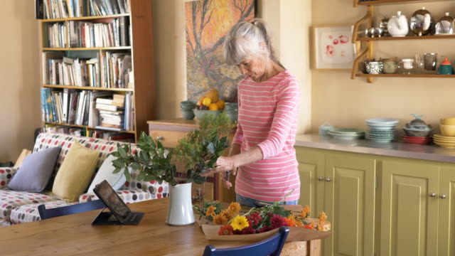 senior woman watching a tutorial video on flower arranging - tutorial stock videos and b-roll footage