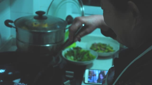 vídeos de stock e filmes b-roll de senior woman watching movie on mobile phone while cooking - chinese culture