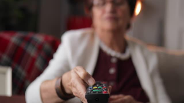 vídeos y material grabado en eventos de stock de senior mujer viendo la televisión y tomar té en casa - abuela