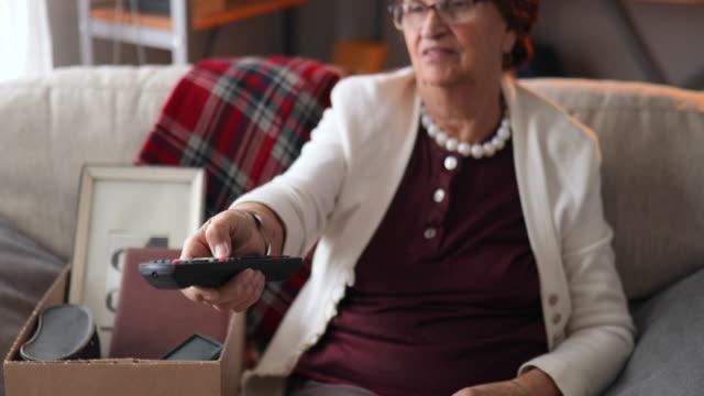 vídeos de stock e filmes b-roll de senior woman watching tv and drinking tea at home - avó