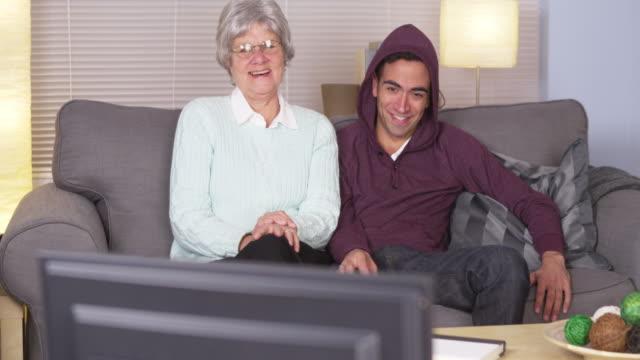 senior woman watching tv with man - プエルトリコ人点の映像素材/bロール