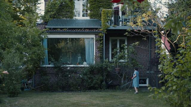 stockvideo's en b-roll-footage met senior woman watering back yard of old villa - dusk