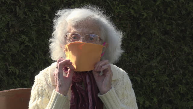 a senior woman wearing a face mask to protect herself from corona virus - part of a series stock videos & royalty-free footage
