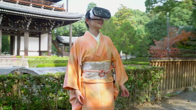 Senior woman wearing a Kimono using a virtual reality headset