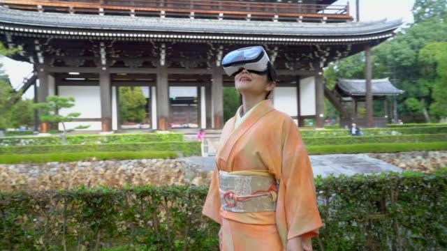 vídeos y material grabado en eventos de stock de senior mujer vestida con un kimono con un casco de realidad virtual - realidad aumentada