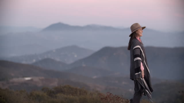 senior woman wearing a poncho hiking in the mountains - fog stock videos & royalty-free footage