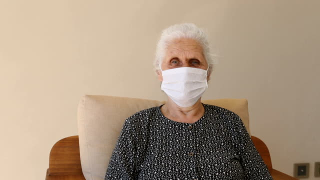 senior woman wearing a protective face mask, sitting and looking at camera - white hair stock videos & royalty-free footage