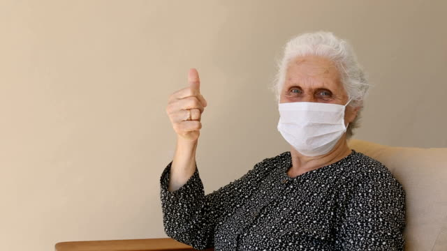 senior woman wearing a protective face mask, sitting, looking at camera and giving thumbs up - white hair stock videos & royalty-free footage