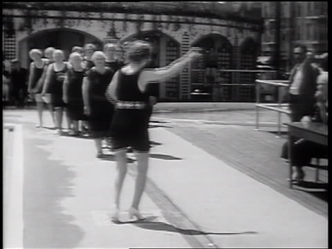 b/w 1939 senior woman wearing bathing suit dancing near swimming pool in senior beauty pageant - spielkandidat stock-videos und b-roll-filmmaterial