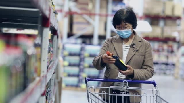 vídeos de stock, filmes e b-roll de idosa usando máscara facial devido ao coronavírus em supermaket - satisfação