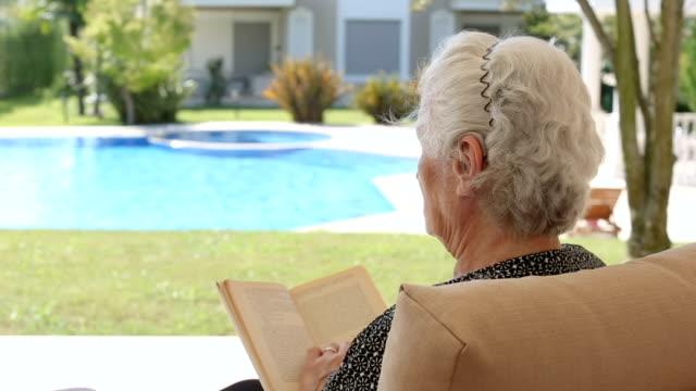 vídeos de stock, filmes e b-roll de idosa usando aparelho auditivo, sentada e lendo um livro em frente a uma piscina no quintal - envelhecido efeito fotográfico