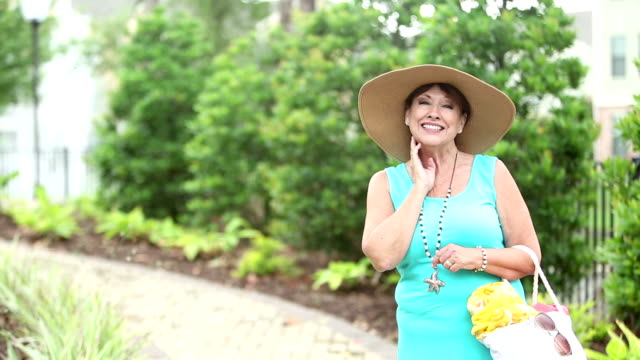 senior woman wearing wide brim hat, carrying beach bag - beach bag stock videos and b-roll footage