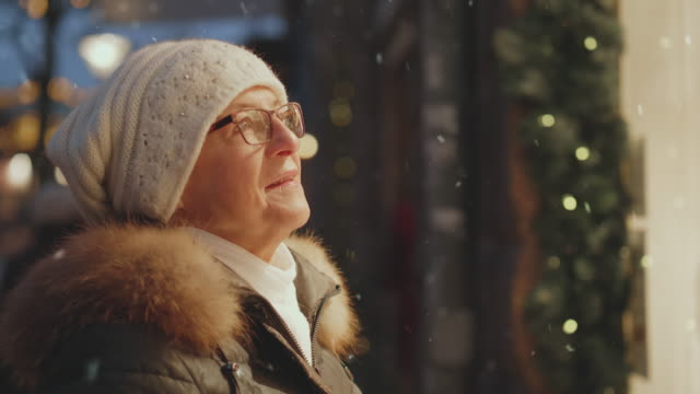 a senior woman window shopping at christmas when its snowing - warm clothing stock videos & royalty-free footage