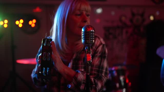vidéos et rushes de femme aîné avec un microphone exécutant sur l'étape avec son groupe - singer