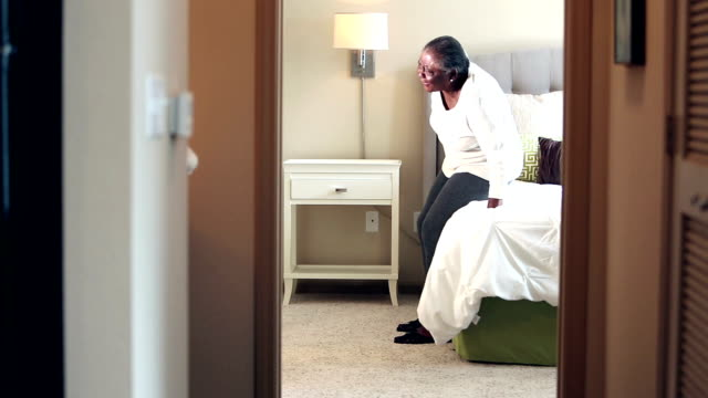 senior woman with backache standing up slowly - woman doorway stock videos & royalty-free footage