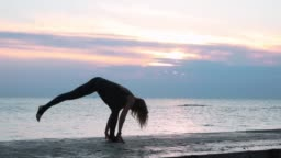 senior woman with beautiful body doing yoga headstand at sunrise on the sea, silhouette of yoga poses