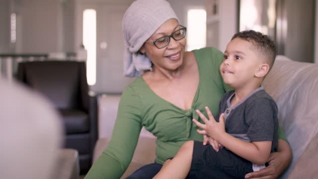 vídeos de stock, filmes e b-roll de mulher sênior com cancro em casa com neto - radioterapia
