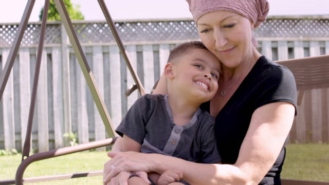 vídeos de stock, filmes e b-roll de mulher sênior com cancro em casa com seu neto - radioterapia