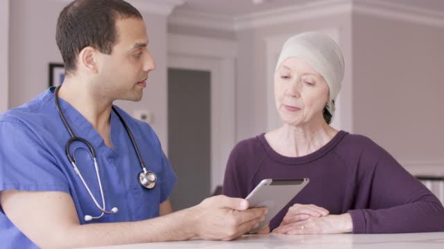 vídeos de stock e filmes b-roll de senior woman with cancer at home with male nurse - cancro