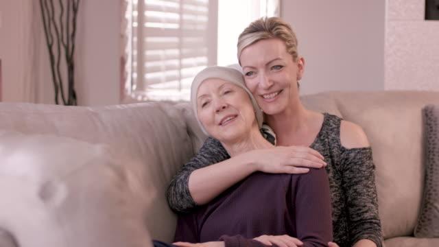 vídeos de stock, filmes e b-roll de mulher sênior com o cancro que está sendo abraçado pela irmã adulta - radioterapia