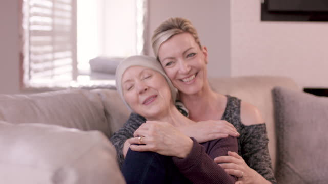 senior woman with cancer being embraced by adult sister - chronic illness stock videos and b-roll footage