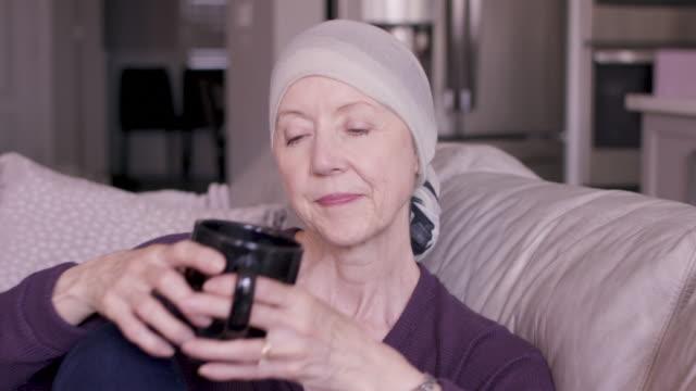 vídeos de stock, filmes e b-roll de mulher sênior com o cancro que bebe uma bebida quente - radioterapia