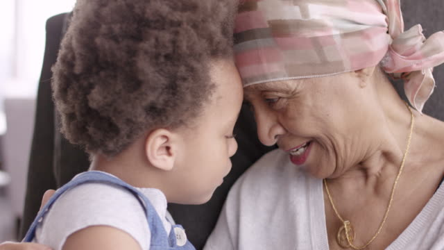 senior woman with cancer lovingly holds granddaughter - grandchild stock videos & royalty-free footage