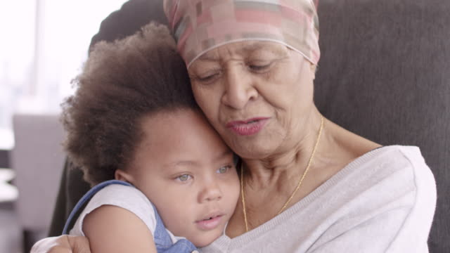 senior woman with cancer lovingly holds granddaughter - cancer illness stock videos & royalty-free footage