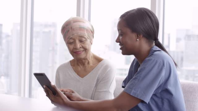 がんのシニア女性は、女性医師との検査結果を確認します - 生存点の映像素材/bロール