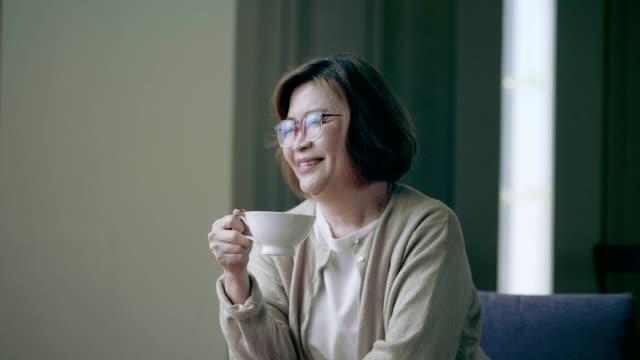 帶著咖啡的高級婦女把目光移開 - looking away 個影片檔及 b 捲影像